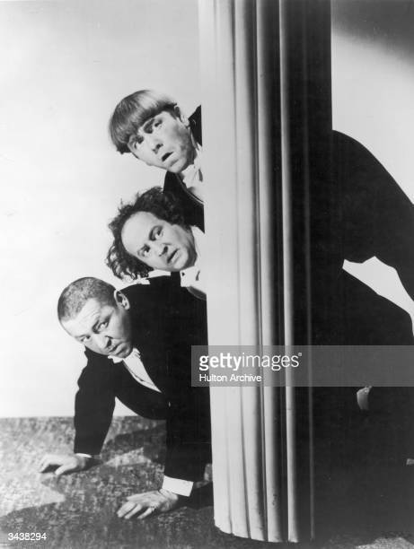 The Three Stooges peer around a column while hiding Top to bottom Moe Howard Larry Fine and Curly Howard