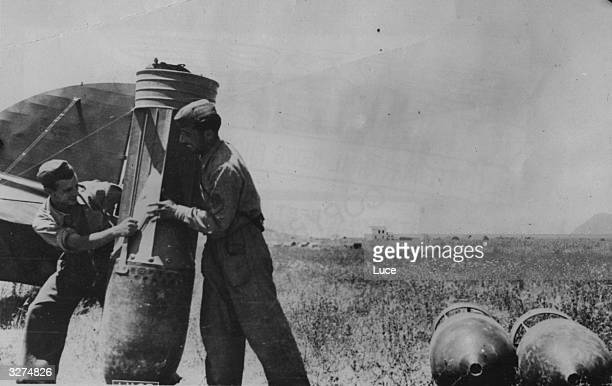 Two Italian airmen laugh as they balance a 2000 lb bomb on its nose The airmen are working from a base in Libya conducting raids on British outposts...