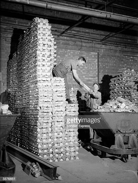 Two men stacking ingots of recycled aluminium in a wharehouse The aluminium has been recycled from pots and pans