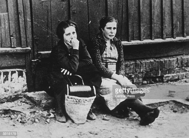 Two women sitting in the street in Warsaw Poland after the German occupation