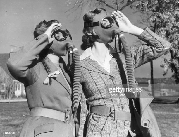 Two women wearing gasmasks