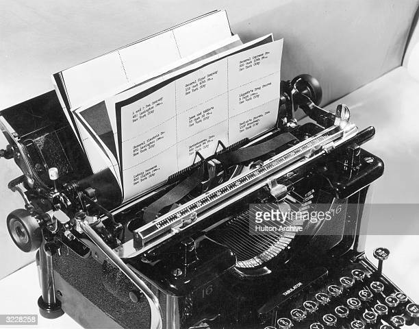 View of a manual typewriter printing a sheet of business labels