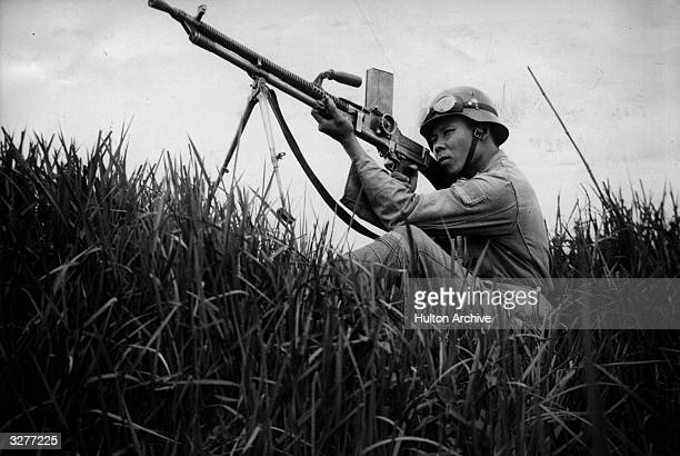 A Japanese soldier takes aim at a plane bombing positions close by