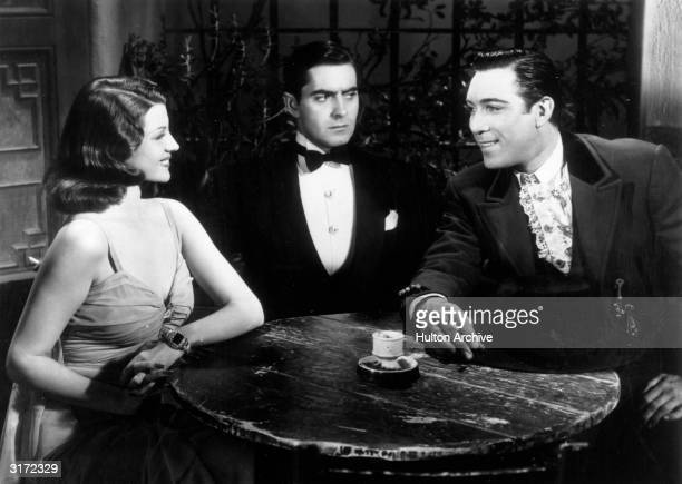 American actors Rita Hayworth Tyrone Power and Mexicanborn actor Anthony Quinn sit at a table in a still from director Rouben Mamoulian's film 'Blood...