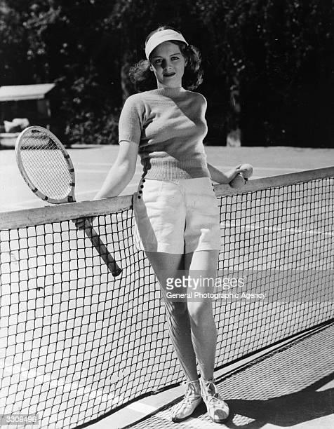 American actress Arleen Whelan posing by a tennis net