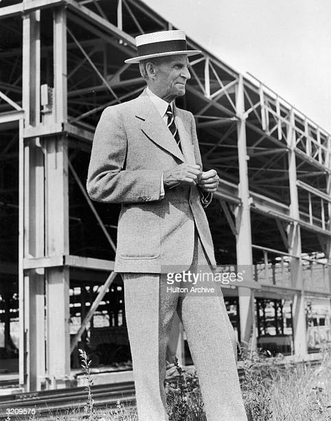American industrialist and inventor Henry Ford posing in front of scaffolding during the construction of a Ford Motors aircraft factory in Willow Run...