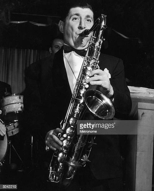 EXCLUSIVE American jazz musician and bandleader Tony Pastor playing the tenor saxophone on a bandstand