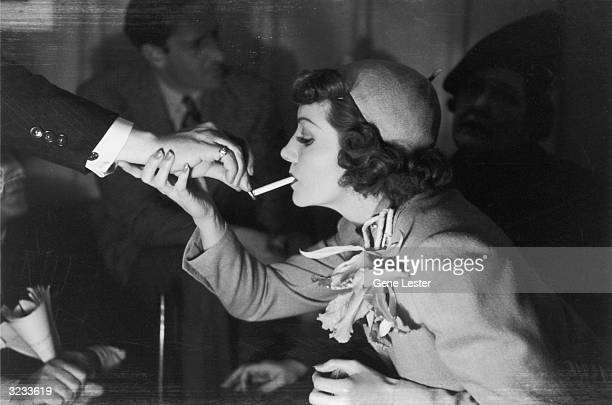 Profile view of French-born actor Claudette Colbert having her cigarette lit.