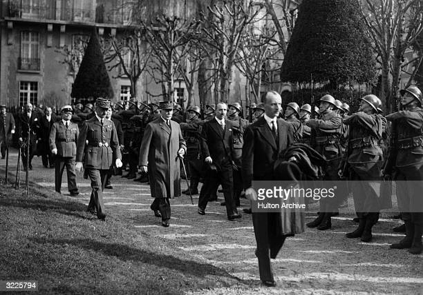 French Vichy chiefofstate Marshal Philippe Petain and Mexican Minister General Francisco Aguilar walk past a battalion of French soldiers in France...
