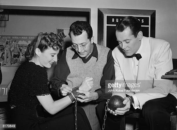Henry Fonda looks on whilst his costar Barbara Stanwyck is fitted with a ball and chain for a scene in the romantic comedy 'The Lady Eve' directed by...