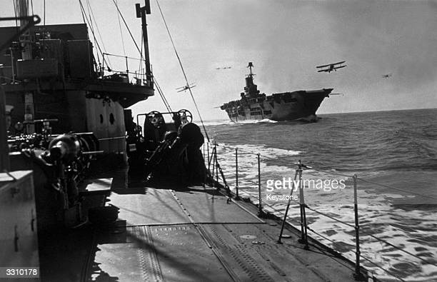 HMS Ark Royal on patrol with planes flying around her deck seen from an accompanying destroyer