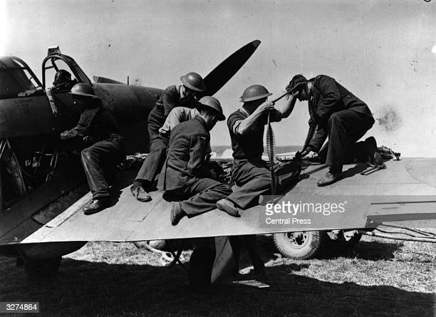 Members of the ground crew at an RAF staion 'somewhere in England' replenishing ammunition on the wing of a Hurricane