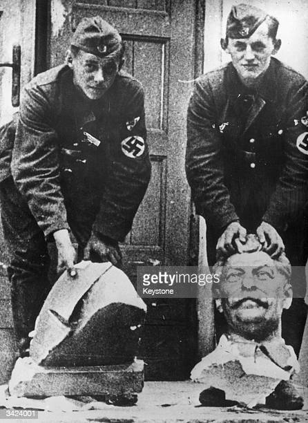 Two young German soldiers on the Russian front with a damaged bust of Stalin