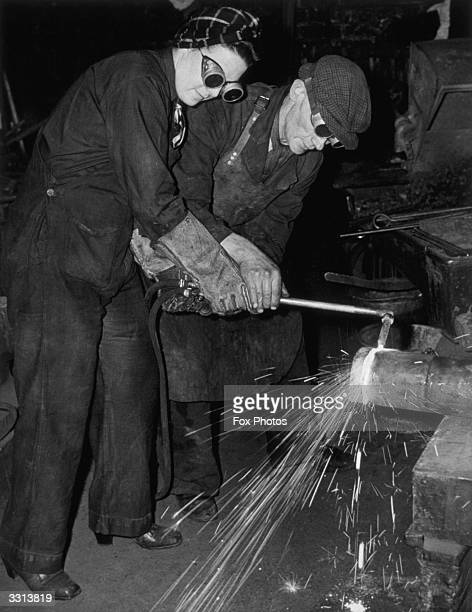 Women are trained for work in war factories at London Transport depots over a period of eight weeks the training includes lathe milling and welding...