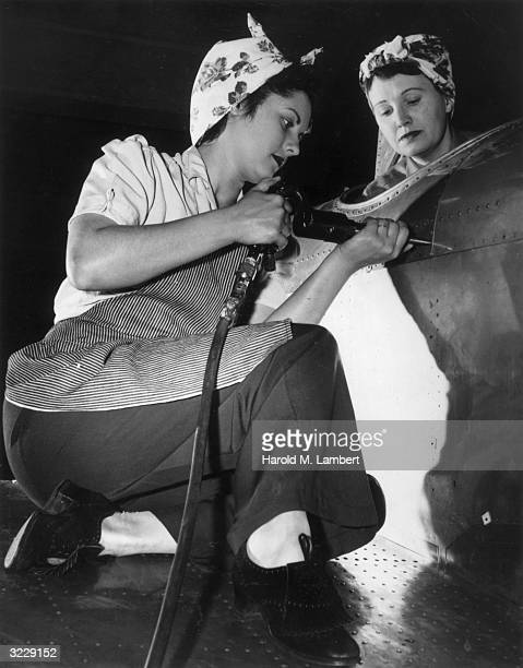 A female factory worker uses an electric riveter while constructing the exterior of an airplane while another female worker watches from the cockpit...