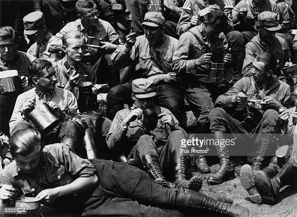 A group of German troops eating their rations from metal tins