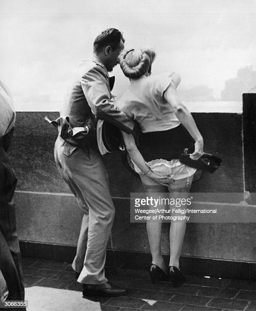 A gust of wind blows a woman's skirt in the air as she admires the view from the top of the Empire State Building New York Photo by...