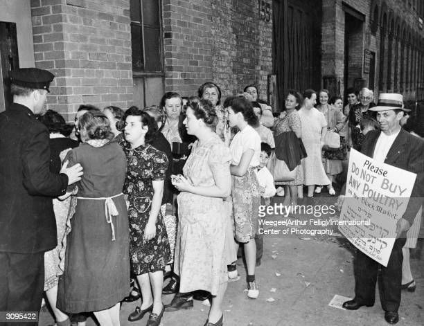 A man standing next to a queue of women in America holds a sign asking people not to buy poultry on the black market during World War II Photo by...