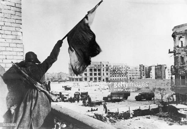 A Russian soldier waves a flag while standing on a balcony overlooking a square where military trucks gather during the Battle of Stalingrad World...
