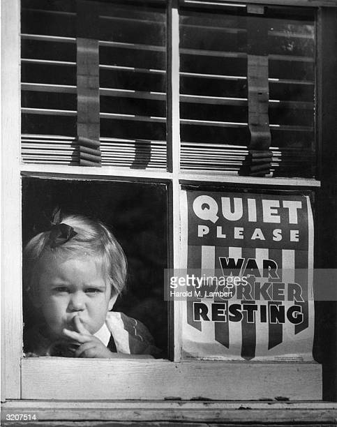 Toddler girl, her faced pressed against a window, gestures for quiet outside the house next to a sign that reads, 'Quiet Please. War Worker...