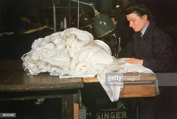 A WAAF woman uses a Singer sewing machine to stitch a bundle of parachute silk
