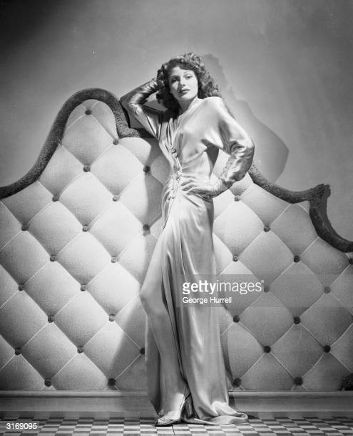 American actress Rita Hayworth wearing a floorlength gown with a slit up the front