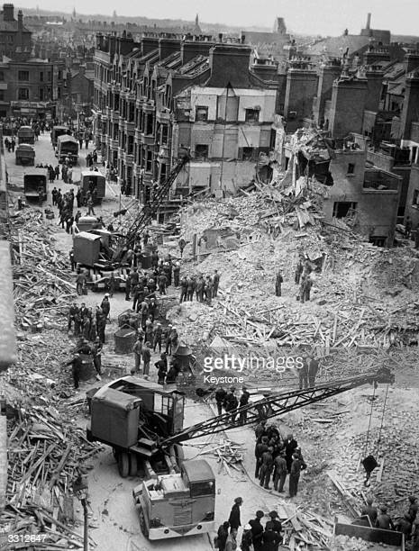 Demolition workers in the Elephant and Castle stop digging when they hear that rescuers have detected somebody under the rubble