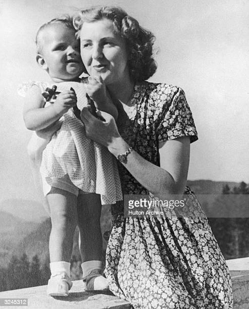 Eva Braun, the German mistress of chancellor Adolf Hitler poses on a terrace with an infant, in a still from a home movie taken by her sister Grete...