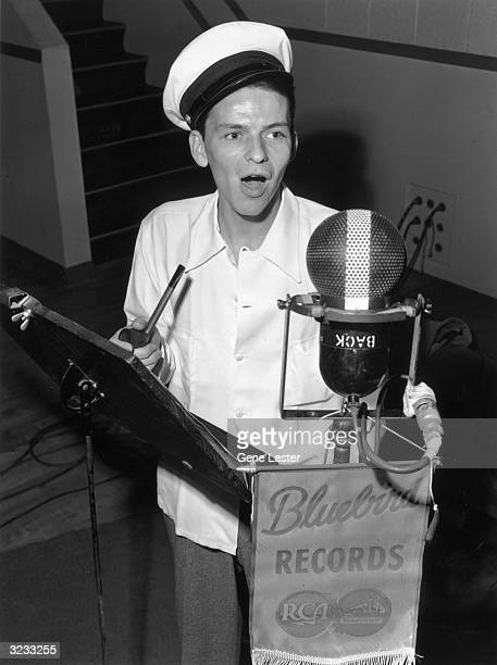 EXCLUSIVE American singer and actor Frank Sinatra stands next to a music stand and holds a pipe as he sings into a microphone during a recording...
