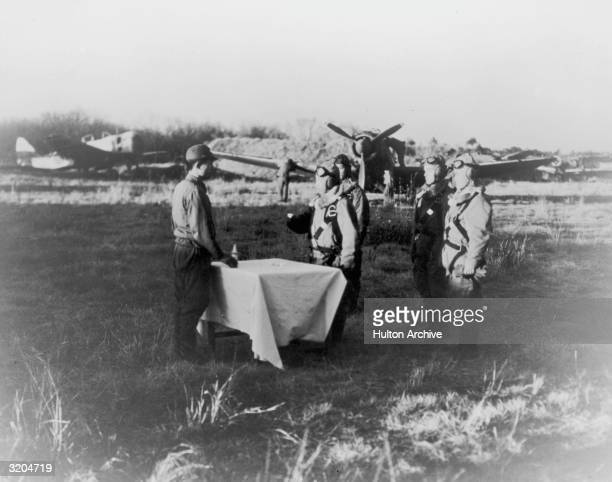 Full-length image of World War II Japanese Kamikaze pilots in a field, drinking ceremonial sake prior to boarding planes for their final mission. The...