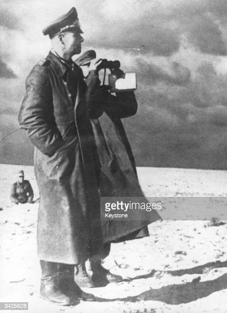 General Rommel stands alongside one of his aides while making a survey of the desert during the Nazi campaign in Libya