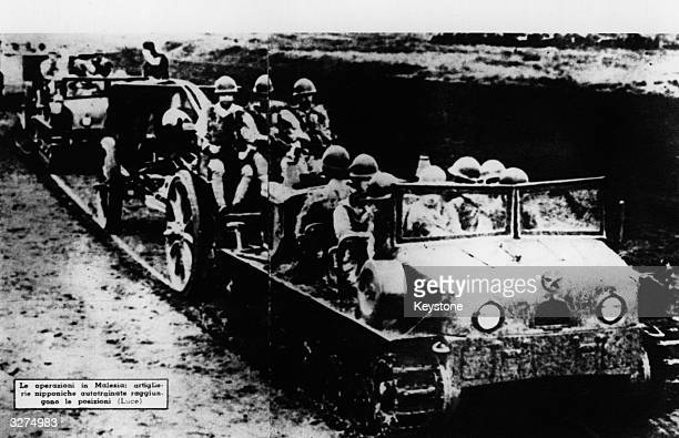 Japanese troops advance with their personnel carriers through Malaya