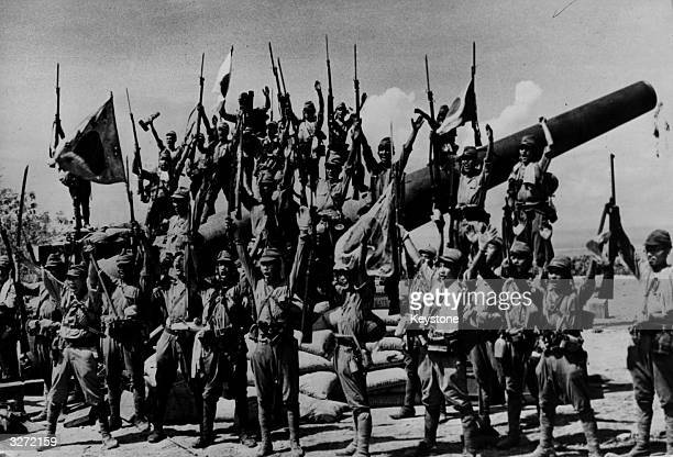 Japanese troops capture a large American gun during the hostilities in Bataan. They are jubilant in their victory.