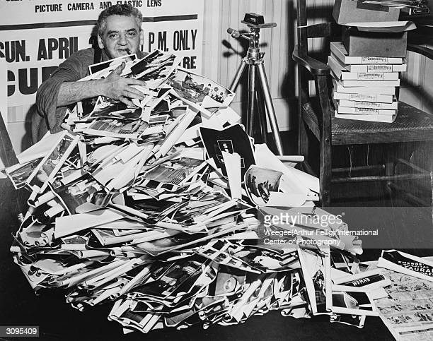 Polish-born American photographer Arthur 'Weegee' Fellig covered by a heap of jumbled photographs. Beside him are a tripod and a pile of photographic...