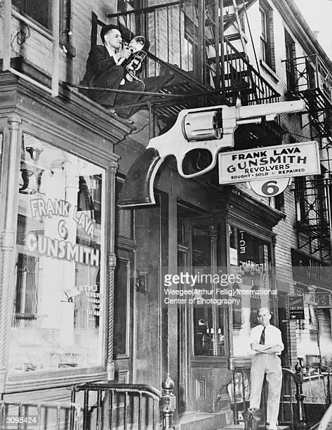 Polish-born American photographer Arthur 'Weegee' Fellig perches on a ledge above Frank Lava's gun shop, 6 center Market Place, Manhattan, New York.