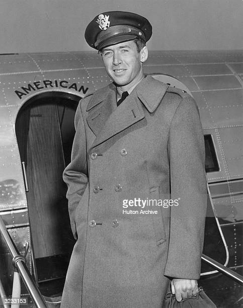 Portrait of American actor Jimmy Stewart in his Air Force cap and wool overcoat in front of a military airplane