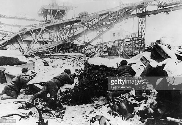Russian soldiers aim their rifles from behind snow-covered rubble as they defend the 'Krasnye Oktyabr' factory from German troops during the Battle...