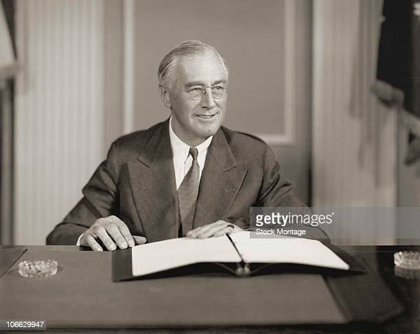 Seated portrait of Franklin D Roosevelt president of the United States who developed government reforms known as the New Deal secured establishment...