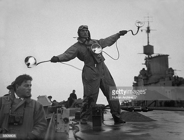 The Deck Landing Officer on HMS Illustrious guides in the pilot of a landing aircraft