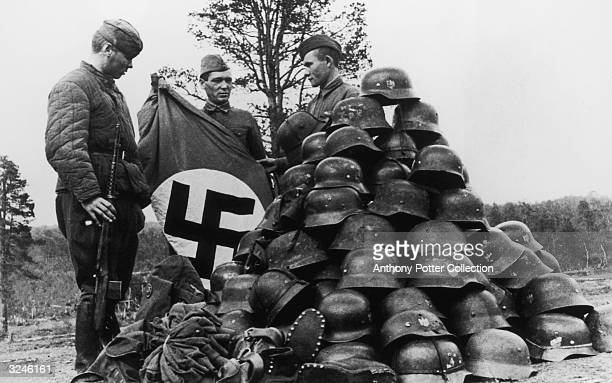 Three Soviet soldiers display a Nazi flag and a pile of military helmets and boots, captured after a German Luftwaffe Field Regiment was destroyed...