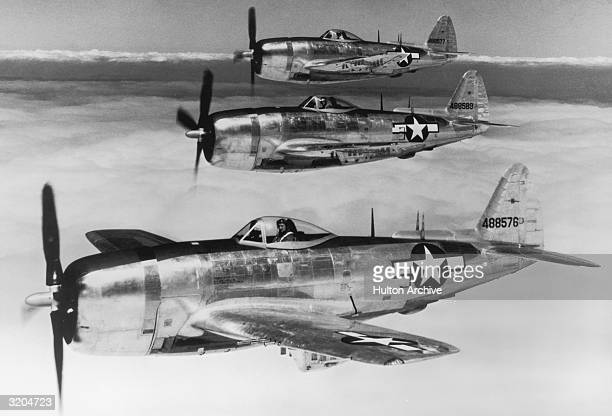 Three U.S. P-47 Thunderbolt fighter planes in the sky above the cloud line, in parallel formation, during the World War II air war in the Pacific.