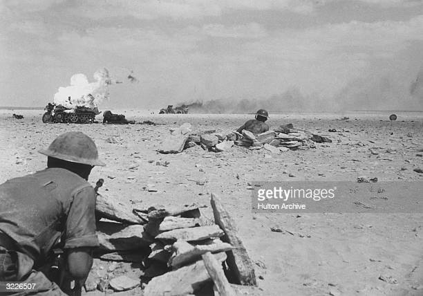 Two Allied soldiers cautiously observe the burning wreckage of two German war vehicles after Rommel's AfrikaKorps retreat in the North African desert...