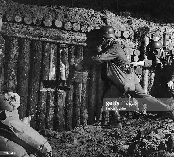 Two German Army storm-troopers wear gas masks as they infiltrate an enemy's log bunker in a military propaganda still, World War II. A machine gun...