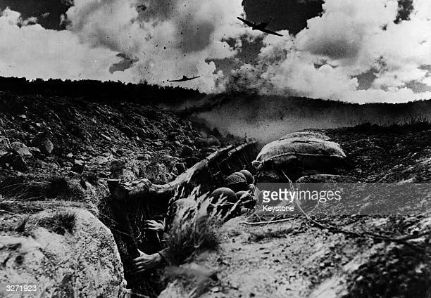 US soldiers undergoing final training before being sent to the front They duck low in a slit trench whilst Allied planes simulate an attack