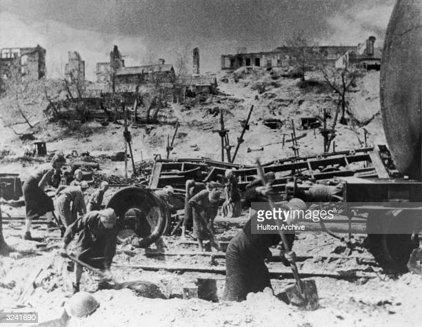 Women digging near damaged train tracks during the Battle of Stalingrad USSR during World War II Many of the women wear babushkas and skirts On the...