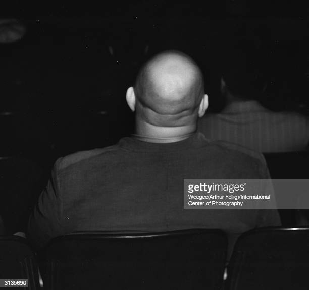 A baldheaded man is captivated by the show at a movie theatre Taken with infrared negative Photo by Weegee/International Center of Photography/Getty...