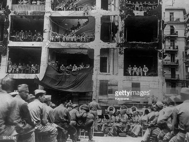A bombblasted building provides the 'boxes' for American soldiers attending an outdoor band concert in Algiers