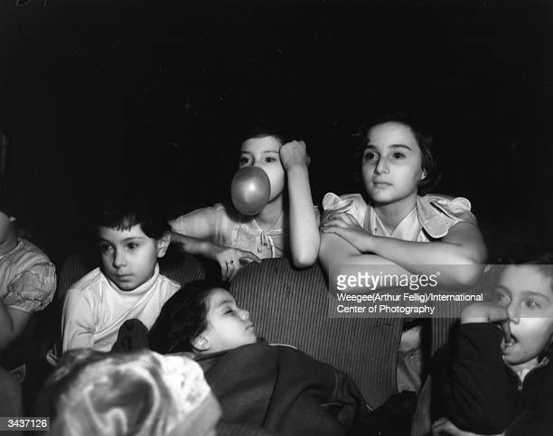 Group of children seem less than enthralled by a film at the Palace Theatre: one falls asleep whilst another blows bubblegum bubbles. Taken with...