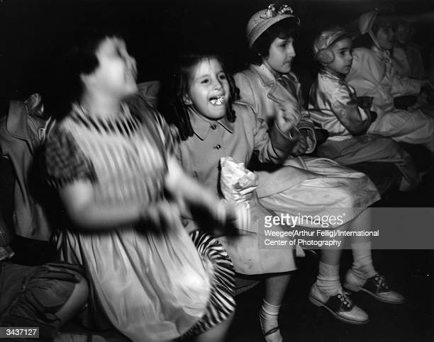 A group of children watching a film at the Palace Theatre One little girl laughs with her mouth full of food Taken with infrared negative Photo by...