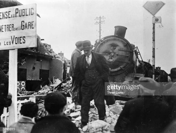 A group of people cluster around a train derailment near Lyons Sabotage by the French resistance was the order of the day